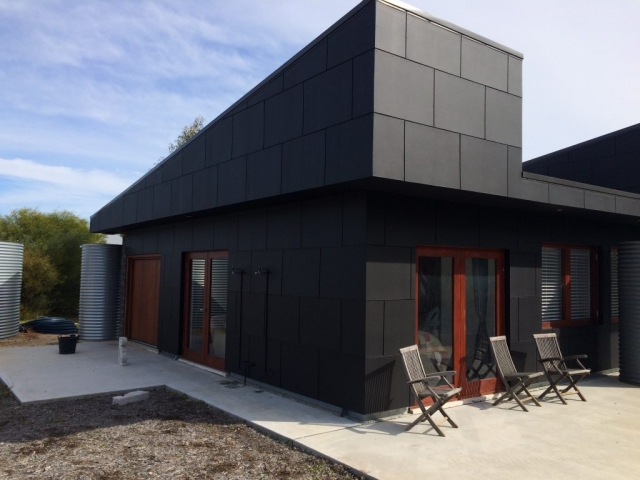 Exterior shot of a dark grey residential painting job