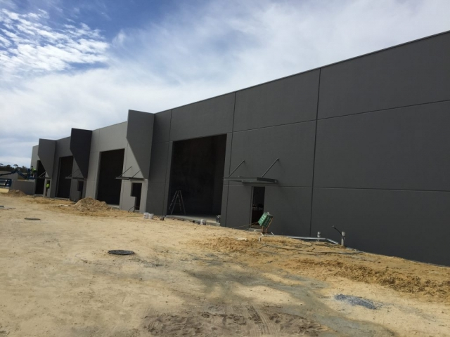 Exterior shot of large commercial building painted in dark grey