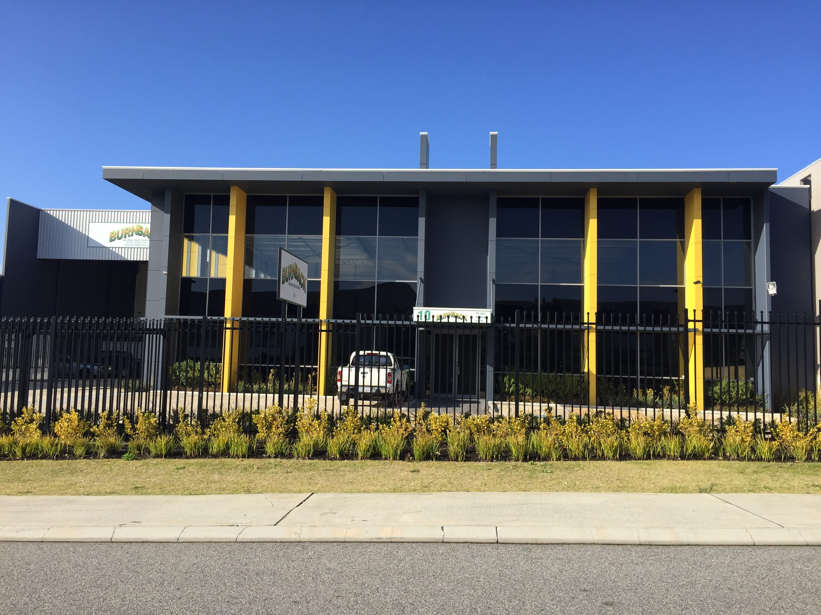 Exterior shot of large commercial office painted in dark grey and finished with yellow accents