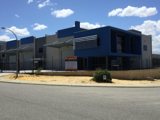 Exterior shot of commercial warehouse office unit, painted in dark blue and grey tones