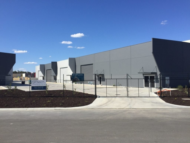 Exterior shot of securely fenced commercial warehouse units, painted in grey and white