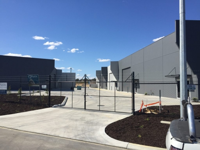 Exterior shot of securely fenced warehouse complex painted in dark grey