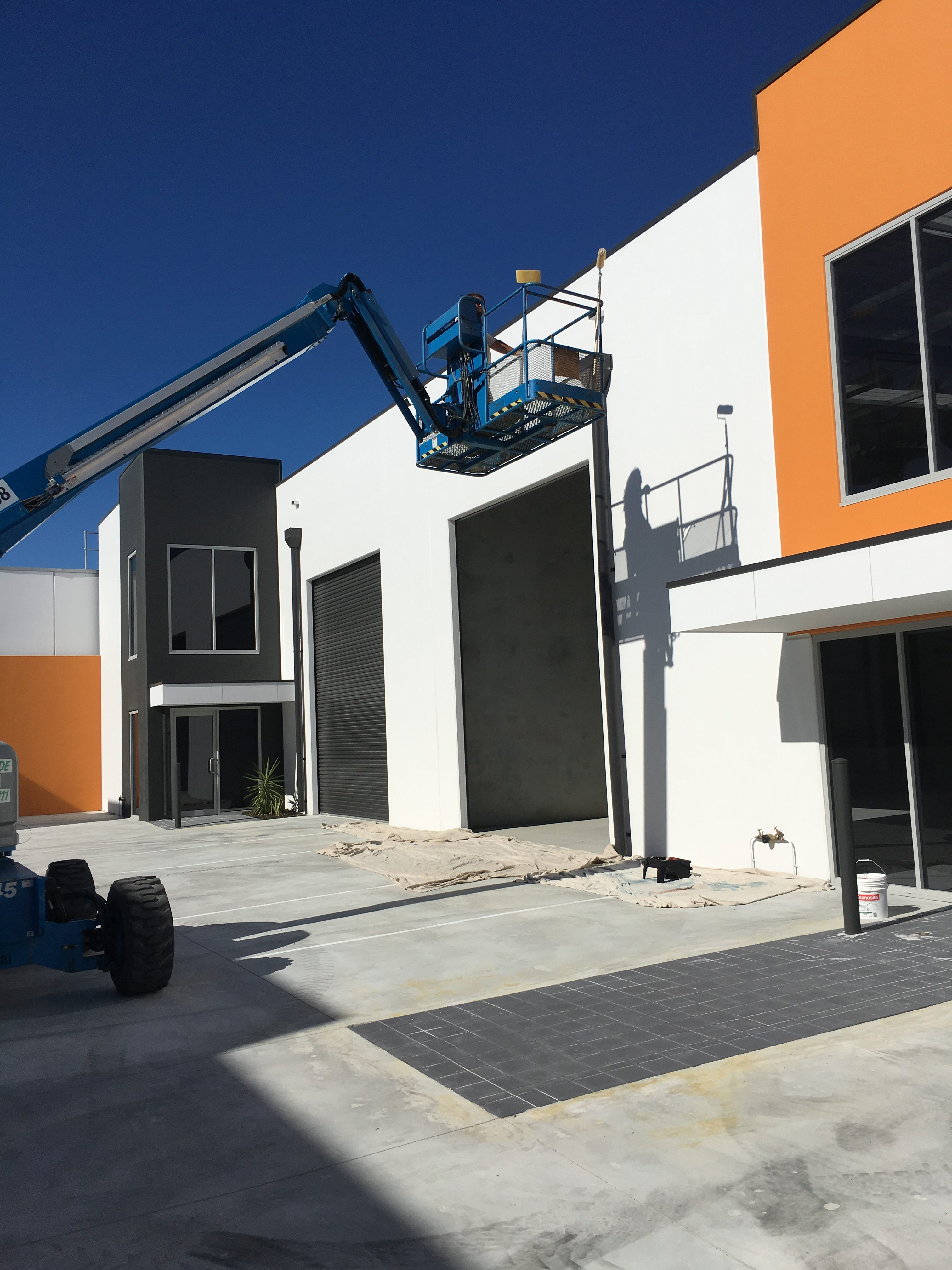 Blue cherry picker parked in front of newly painted commercial warehouse unit finished in white and orange