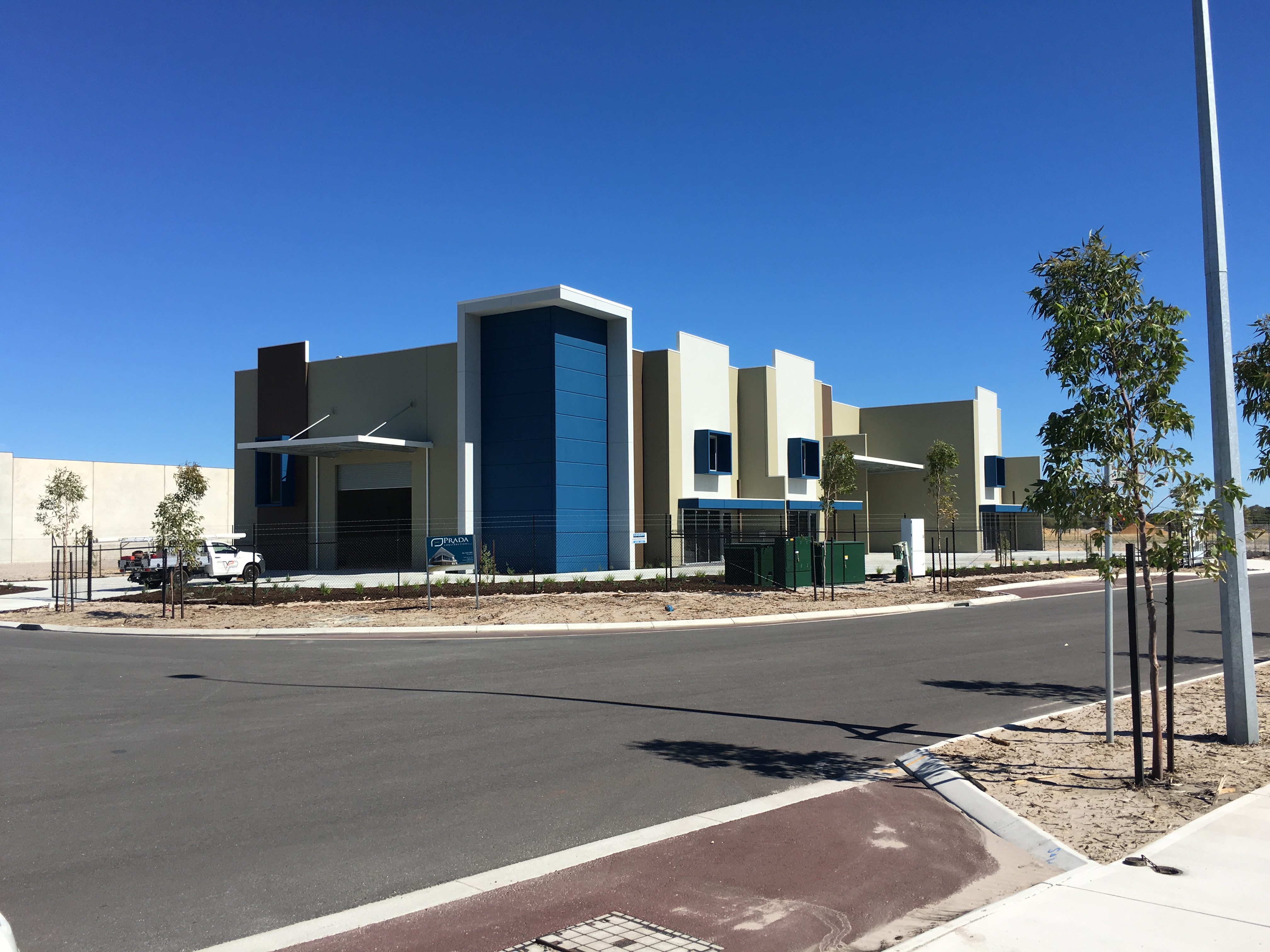 Exterior shot of block of commercial warehouse units, painted in blue, browns and white