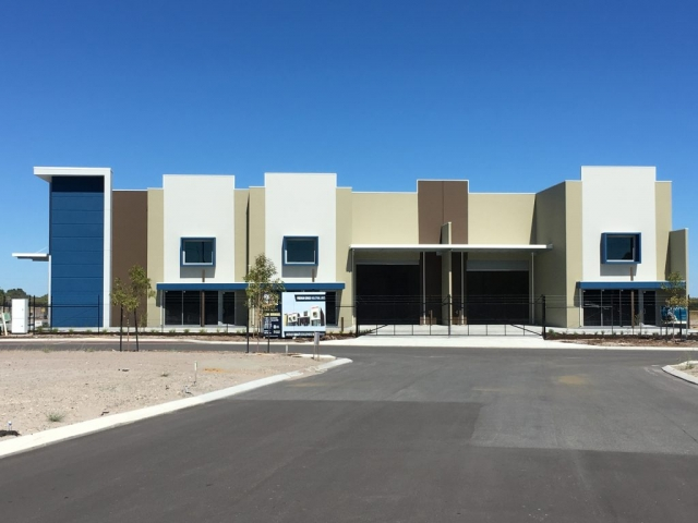 Exterior shot of commercial warehouse unit, painted in tones of blue, brown, cream and white