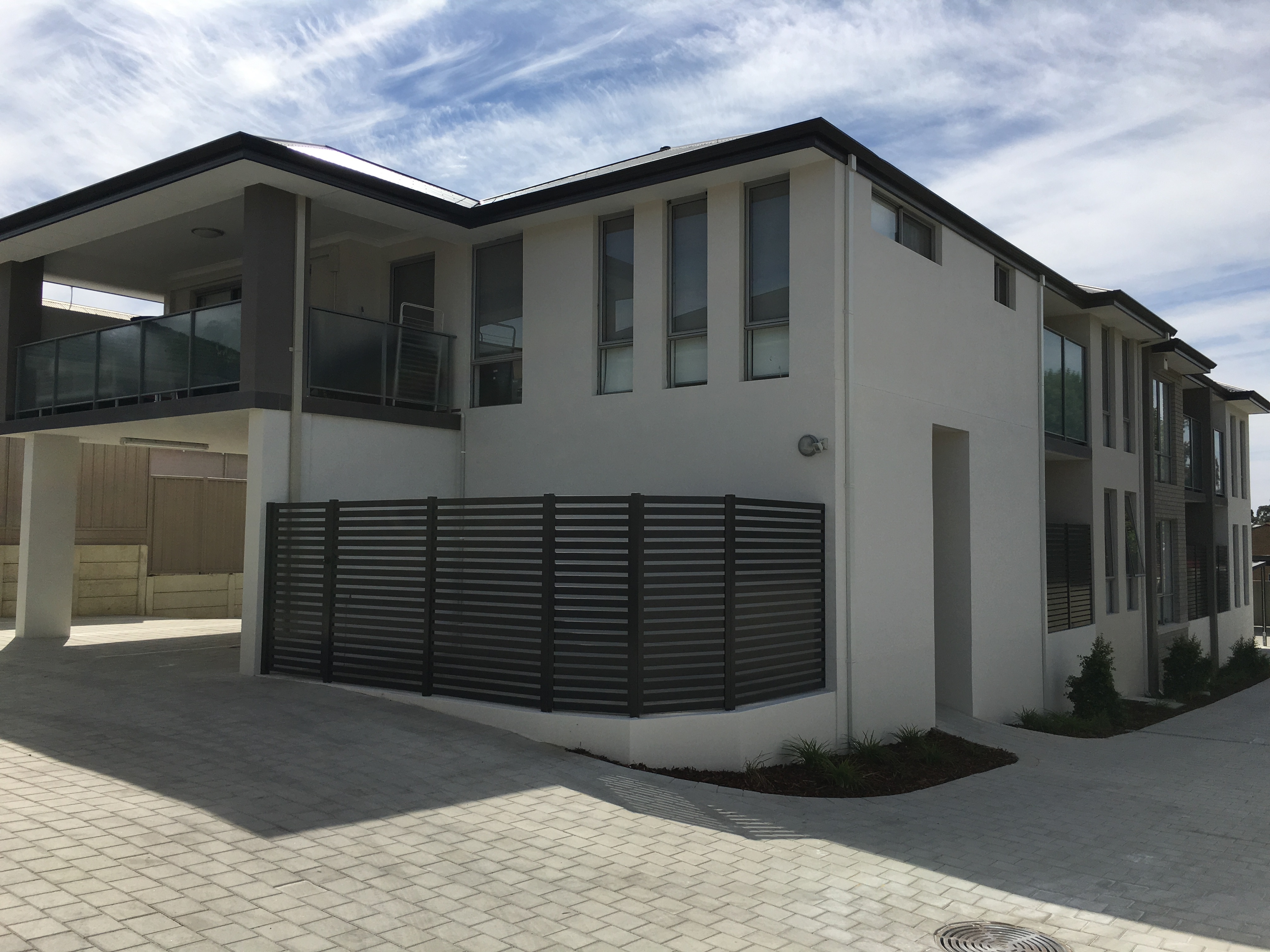 Exterior shot of large residential unit development painted in light grey with dark grey accents