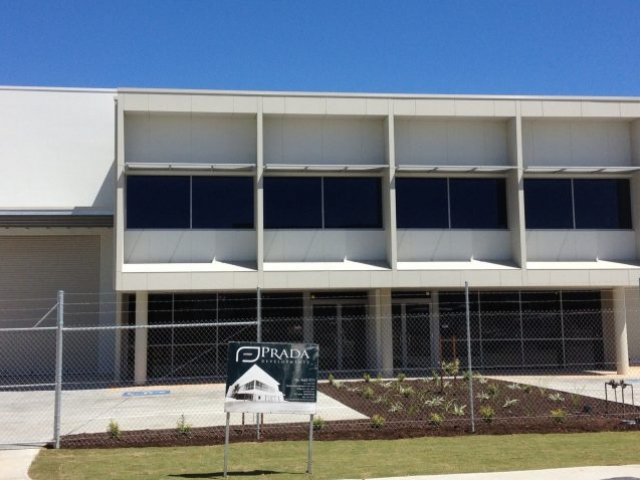 Exterior shot of large commercial warehouse office painted in cream and surrounded by a wire fence