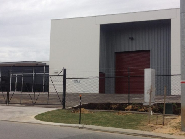 Exterior of large commercial garage and office, painted in grey and maroon and features a security fence