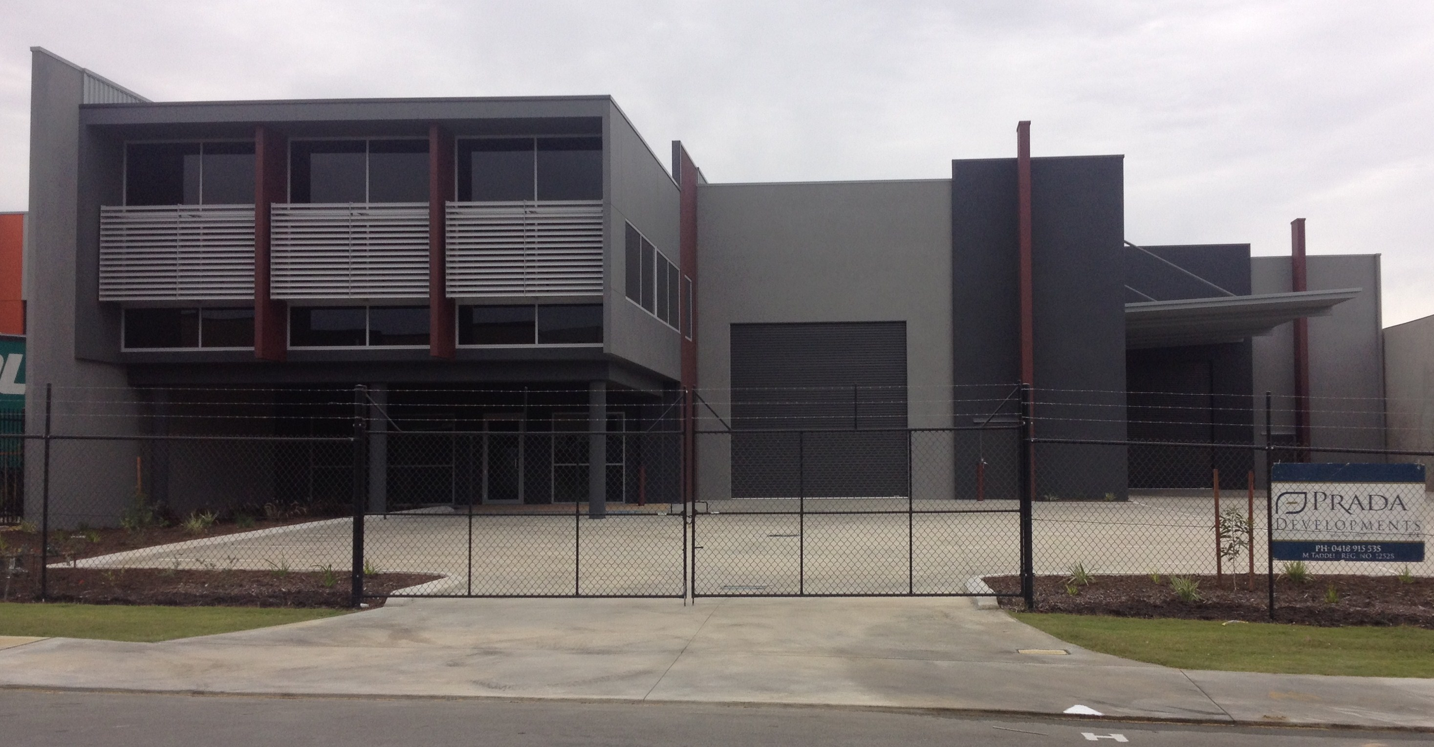 Exterior of securely fenced commercial property painted in shades of grey