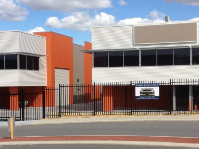 Exterior shot of twin warehouse office units, finished in white and orange paint