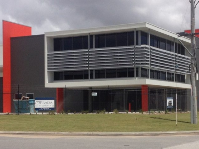 Exterior of commercial office building, finished in dark grey and red paint